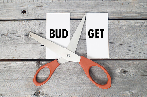 "scissors cutting the word ""budget"" in half"