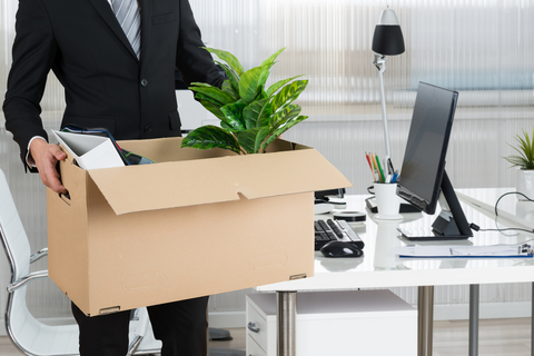 man holding box of belongings leaving his office
