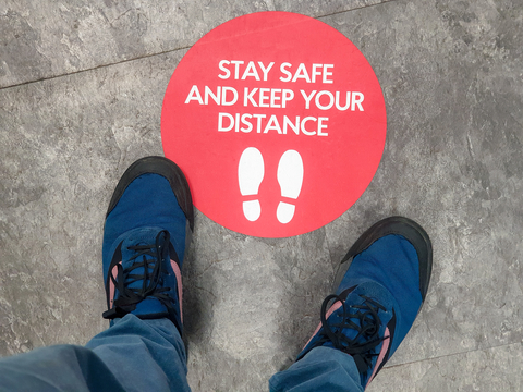 Social distancing sign with two feet standing on it