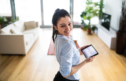 A woman holding a tablet with smart home screen at home