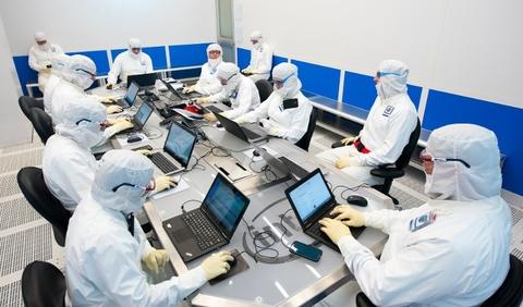 guys in clean room gear on laptops
