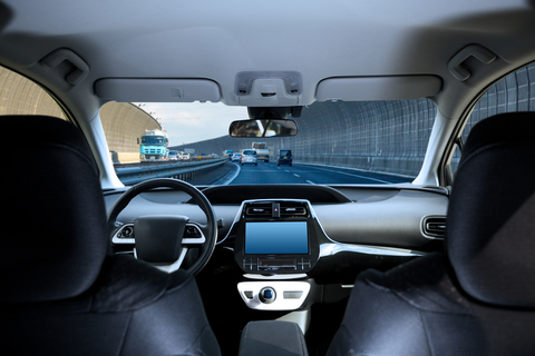 Cockpit of driverless car driving on highway viewed from rear seat