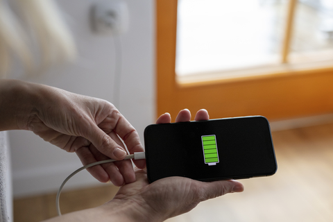 Hands holding smart phone with fully charged battery icon
