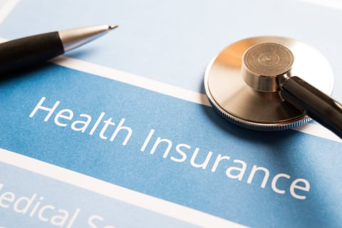 Health insurance, pen and stethoscope
