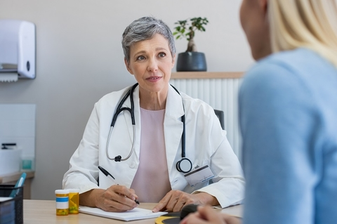 A mature woman physician consulting with a patient in the doctor's office.