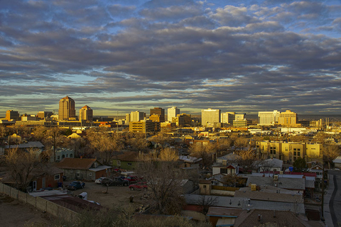 The downtown city skyline of Albuquerque, New Mexico early in the morning as the sun illuminates the buildings with a golden glow.