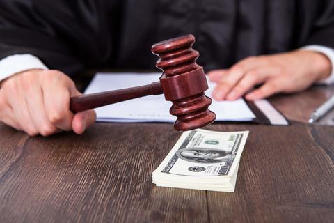 Judge banging gavel on stack of money