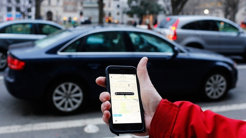 An Uber application is shown as cars drive by in Washington, DC