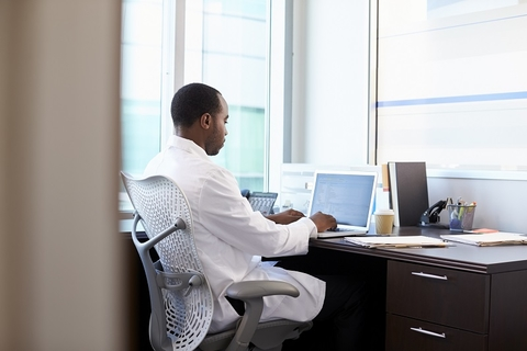A doctor sitting at his desk working on a laptop computer.