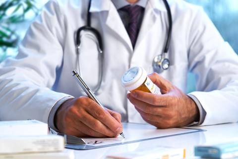 A coctor writing a prescription
