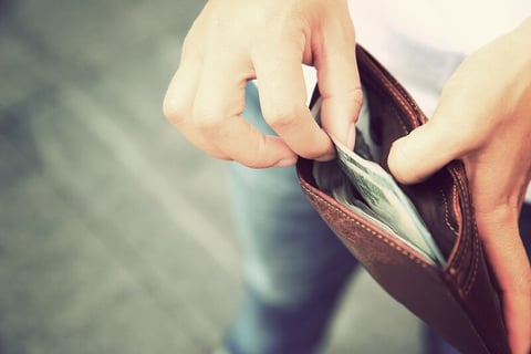 A man taking cash out of his wallet
