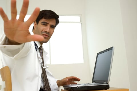 A doctor at a desk holding up his hand to say stop