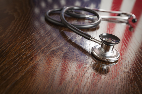 Stethoscope on wooden table with American flag reflected on the wood