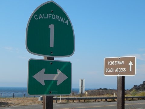 "Sign for the 1 (freeway) and sign reading ""pedestrian beach access,"" both with arrows, in California, with beach in background"