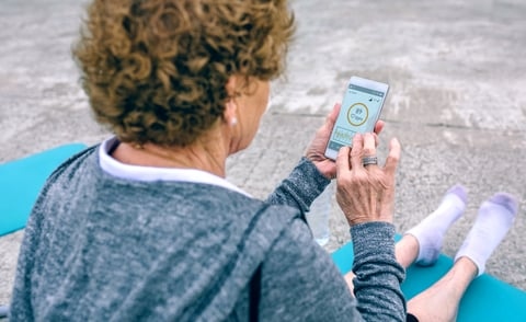 A senior woman sitting on a yoga mat looks at a smartphone with information about heart rate.