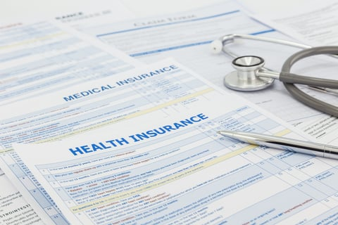Stack of health insurance application forms with stethoscope on top