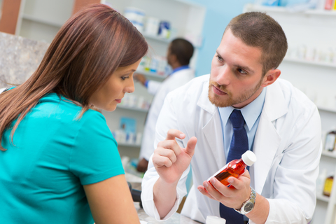 A pharmacist consulting with a patient holding medication