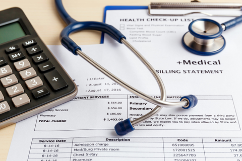 Stethoscope and calculator on top of medical bill