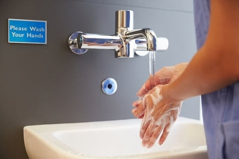 A medical worker washing her hands at a sink.