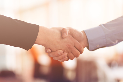 Close-up of handshake between person in suit and person in business shirt.