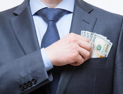 Businessman putting cash in suit pocket