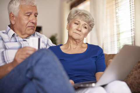 Senior man and woman looking at laptop with confused expressions