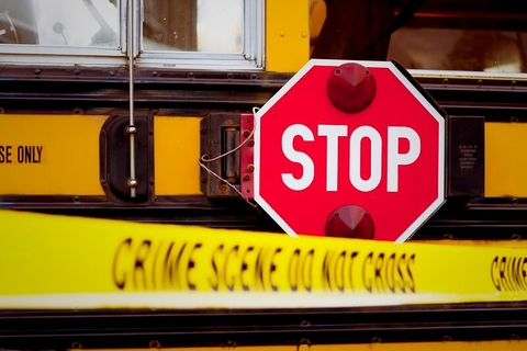 """The side of a school bus with cordon tape that reads """"CRIME SCENE DO NOT CROSS"""""""
