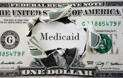 """Dollar bill with a hole in Washington's face on it and the word """"Medicaid"""" in its place"""