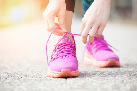 Close-up of hands tying laces on bright pink athletic shoes