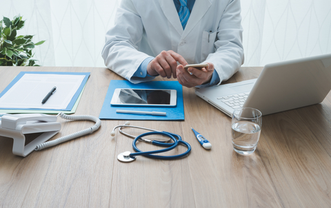 Doctor at desk with notes, smartphone, tablet, computer, and stethoscope