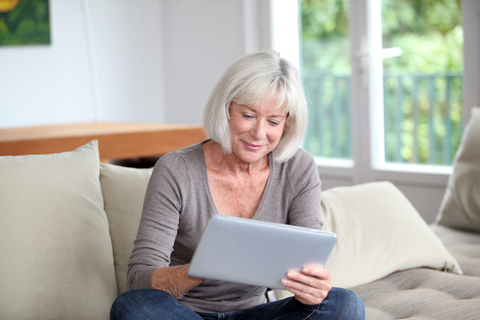 a senior woman sitting on a couch using a tablet