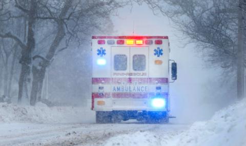 An ambulance drives through winter weather