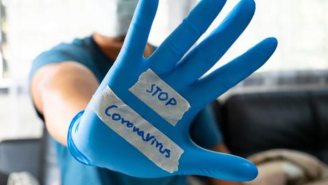 Stop coronavirus message on a gloved hand