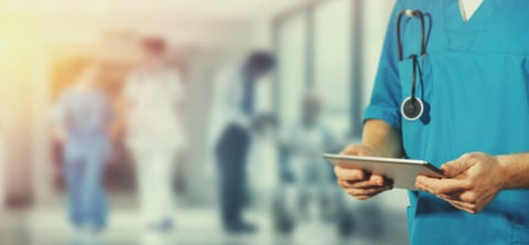 photo shows torso of hospital doctor in hallway holding tablet computer