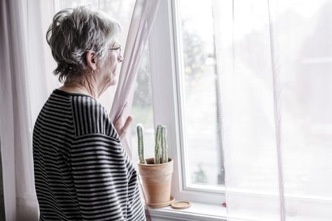 An elderly woman looking out a window