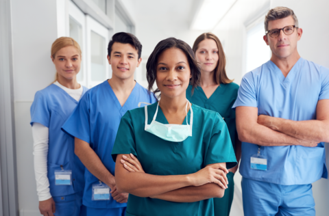 A group of nurses looks at the camera.