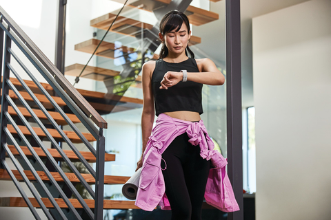 woman dressed to exercise walks down stairs looking at Fitbit fitness tracker on her wrist