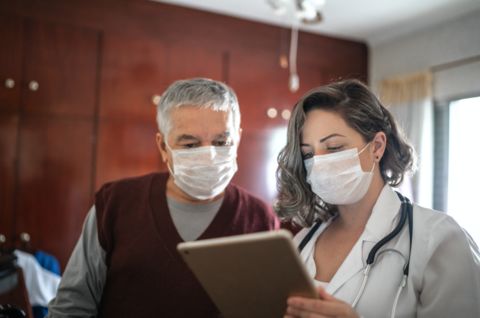 Doctor in mask shows a tablet to a patient in a mask.