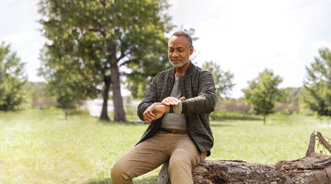 older man places his hand over Fitbit smartwatch device to detect stress levels