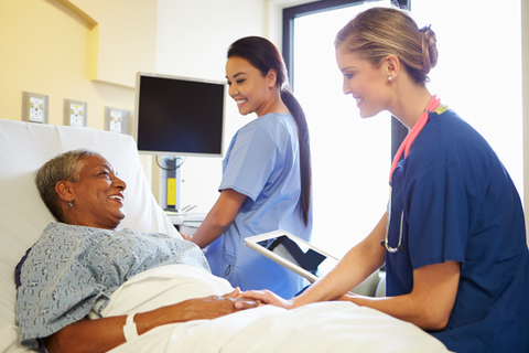 Nurse with tablet talking to senior woman in hospital bed