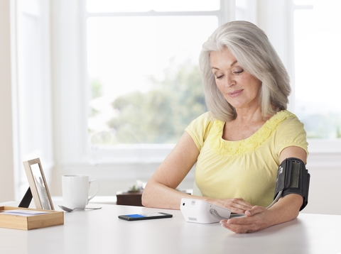 Senior woman sitting at a table using blood pressure monitor device