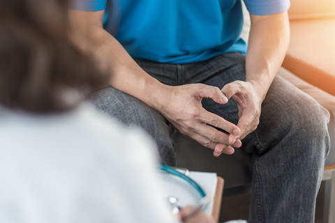 Male patient sitting in chair having consultation with doctor or psychiatrist