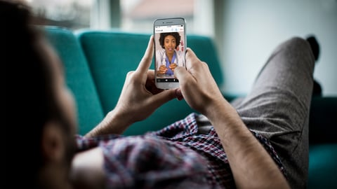 man laying on couch talks with a female doctor using a telehealth app on his smartphone