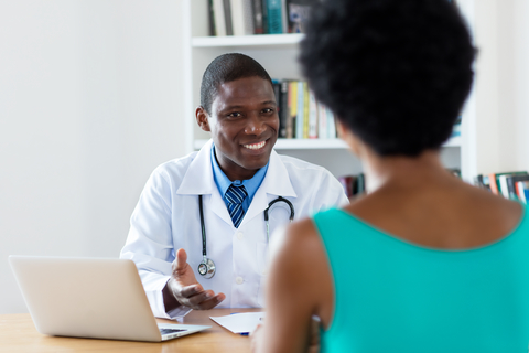 doctor sitting at desk consulting with patient