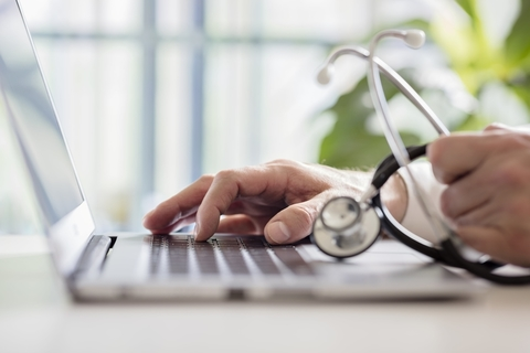A doctor's hand on a keyboard