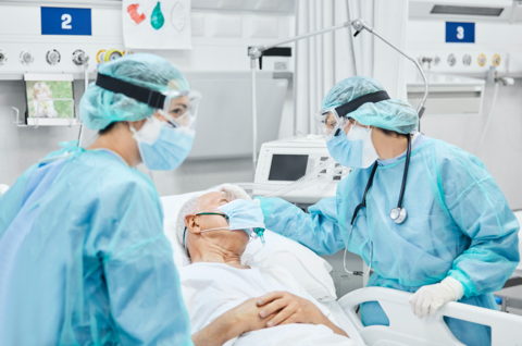Providers in PPE care for patient in hospital bed