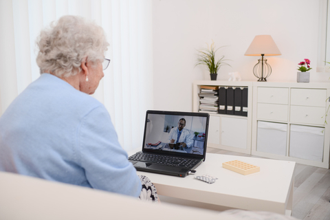 An elderly woman has a virtual visit with her doctor
