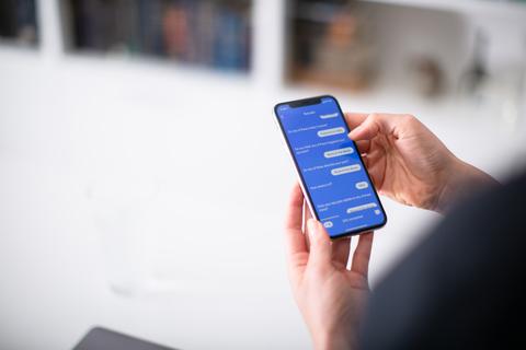 a consumer holds a smartphone and screen shot shows K Health's symptom checker app