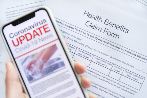 A person fills out a health insurance claim while reading COVID-19 news on a phone