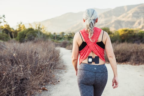 An older woman outdoors hiking wears an Enso medical device on her back to alleviate pain
